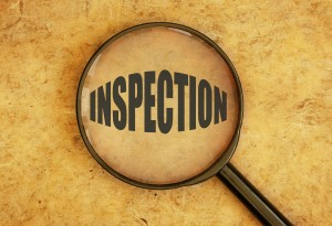 Magnifying glass focusing on the word inspection